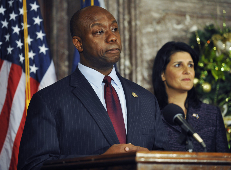 Photo - United States Rep. Tim Scott, left, speaks during a news conference as South Carolina Gov. Nikki Haley looks on at the Statehouse on Monday, Dec. 17, 2012, in Columbia, S.C.  Haley announced Scott as Sen. Jim DeMint's replacement in the U.S. Senate during the news conference, making Scott the only black Republican in Congress and the South's first black Republican senator since Reconstruction. (AP Photo/Rainier Ehrhardt)