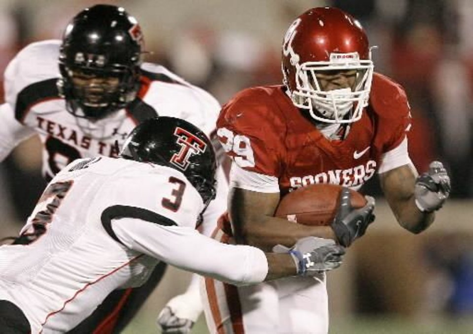 Photo - OU's Chris Brown fights off Jamar Wall of  Texas  Tech during the college football game between the University of Oklahoma Sooners and  Texas  Tech University at Gaylord Family -- Oklahoma Memorial Stadium in Norman, Okla., Saturday, Nov. 22, 2008. BY BRYAN TERRY, THE OKLAHOMAN
