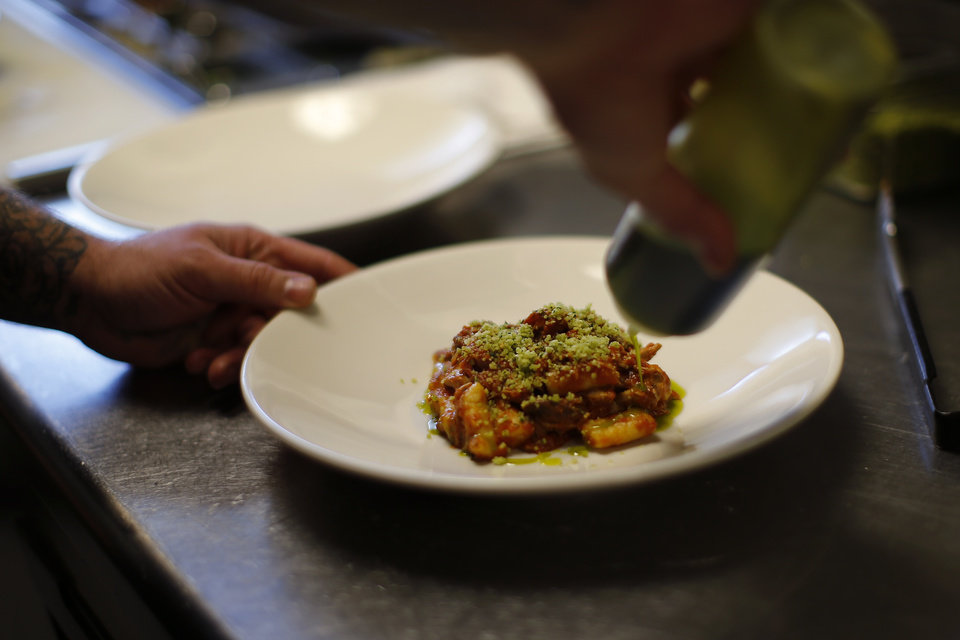 Photo -  Chef Jonathan Krell works on a dish in the kitchen at Patrono in Oklahoma City. [Photo by Bryan Terry, The Oklahoman]