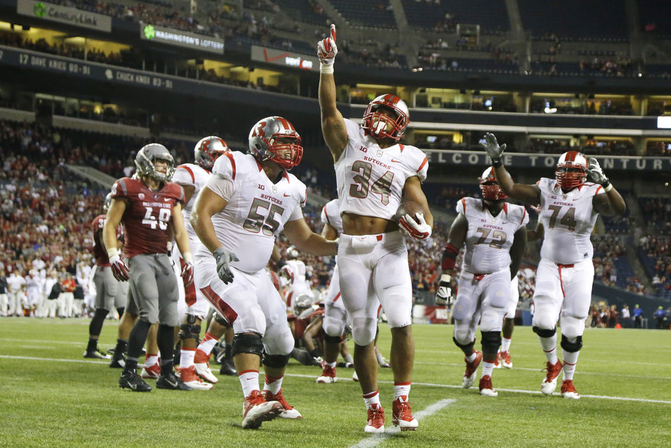 Photo - Rutgers running back Paul James (34) points upward after he rushed for a touchdown in the second half of an NCAA college football game against Washington State, Thursday, Aug. 28, 2014, in Seattle. Rutgers beat Washington State 41-38.  (AP Photo/Ted S. Warren)