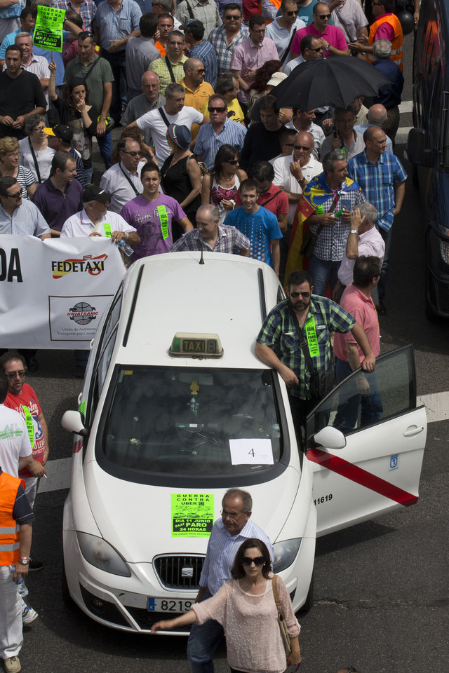 Photo - A taxi leads a demonstration during a 24 hour taxi strike and protest in Madrid, Spain, Wednesday, June 11, 2014. The taxi drivers were protesting against unregulated competition from private companies, in particular, Uber, an international company that puts people in contact with each other to share cars or pay for short journeys in private vehicles within the city. (AP Photo/Paul White)
