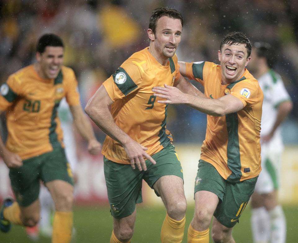 Photo - Australia's Josh Kennedy, center, celebrates with teammate Tommy Oar, right, after Kennedy scored against Iraq during their World Cup soccer Asian qualifying match at the Sydney Olympic Stadium in Sydney, Australia, Tuesday, June 18, 2013. Australia won the match 1-0 and qualify for the 2014 World Cup in Brazil. (AP Photo/Rick Rycroft)