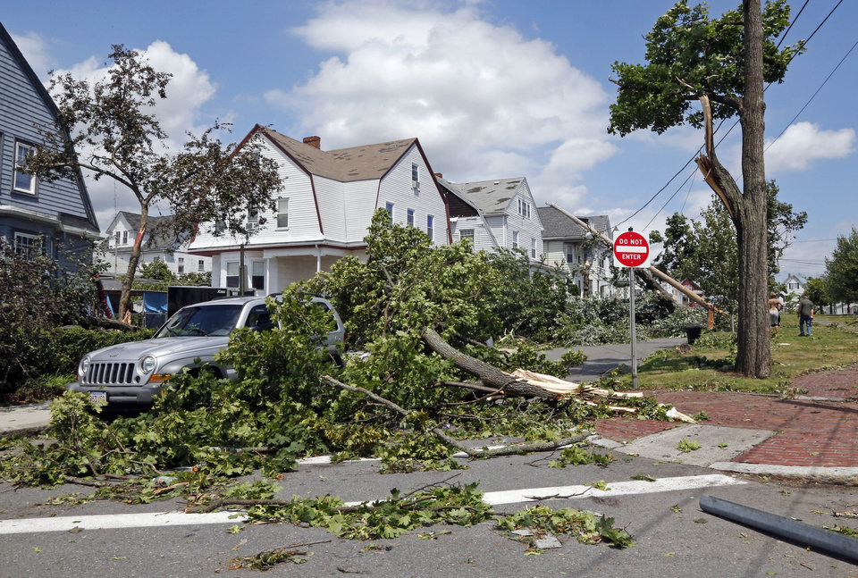 Photo - Downed trees and power lines lay in front of homes in Revere, Mass., Monday, July 28, 2014 after a tornado touched down. Revere Deputy Fire Chief Mike Viviano says the fire department in that coastal city has received dozens of calls reporting partial building and roof collapses, and downed trees and power lines. Viviano says there are no immediate reports of deaths or serious injuries. (AP Photo/Elise Amendola)