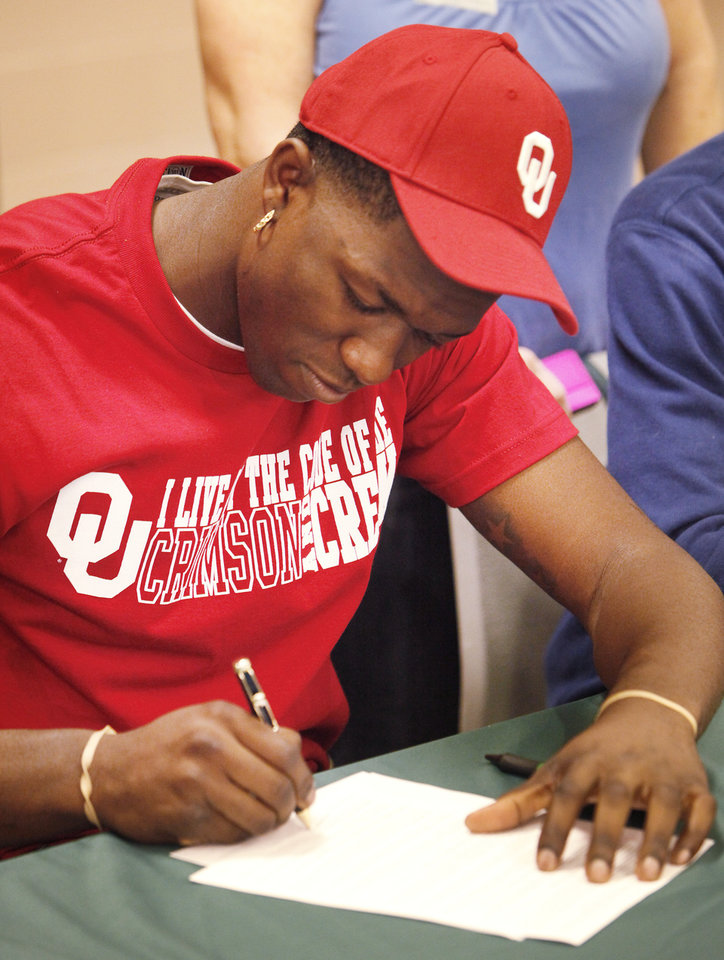 Photo - NATIONAL SIGNING DAY / SIGN / SIGNED: Edmond Santa Fe's Michael Onuoha signs a football letter of intent with the University of Oklahoma (OU), Wednesday, February 1, 2012.Photo by David McDaniel, The Oklahoman
