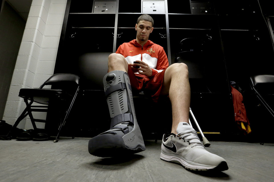 Photo - Iowa State's Georges Niang looks at his phone as he sits in the locker room before an NCAA college basketball tournament practice Saturday, March 22, 2014, in San Antonio. Niang, who broke his foot during Friday's game against North Carolina Central, with not play when Iowa State plays North Carolina Sunday. (AP Photo/David J. Phillip)