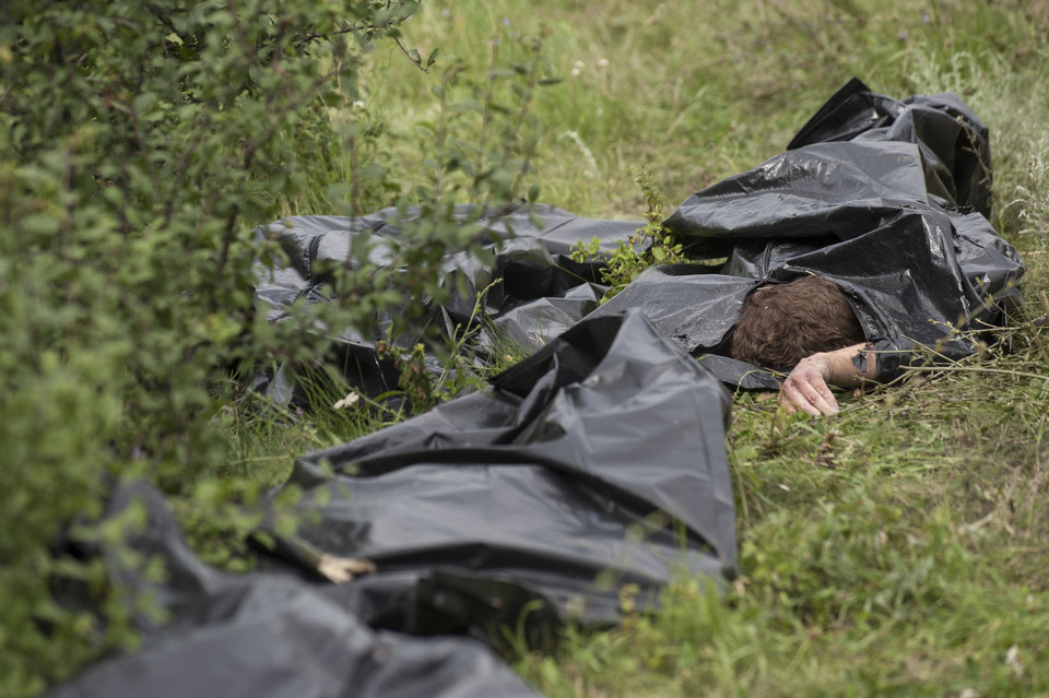 Photo - Bags with victims' bodies lie at the crash site of a Malaysia Airlines jet near the village of Hrabove, eastern Ukraine, Saturday, July 19, 2014. Ukraine accused Russia on Saturday of helping separatist rebels destroy evidence at the crash site of a Malaysia Airlines plane shot down in rebel-held territory — a charge the rebels denied. (AP Photo/Evgeniy Maloletka)
