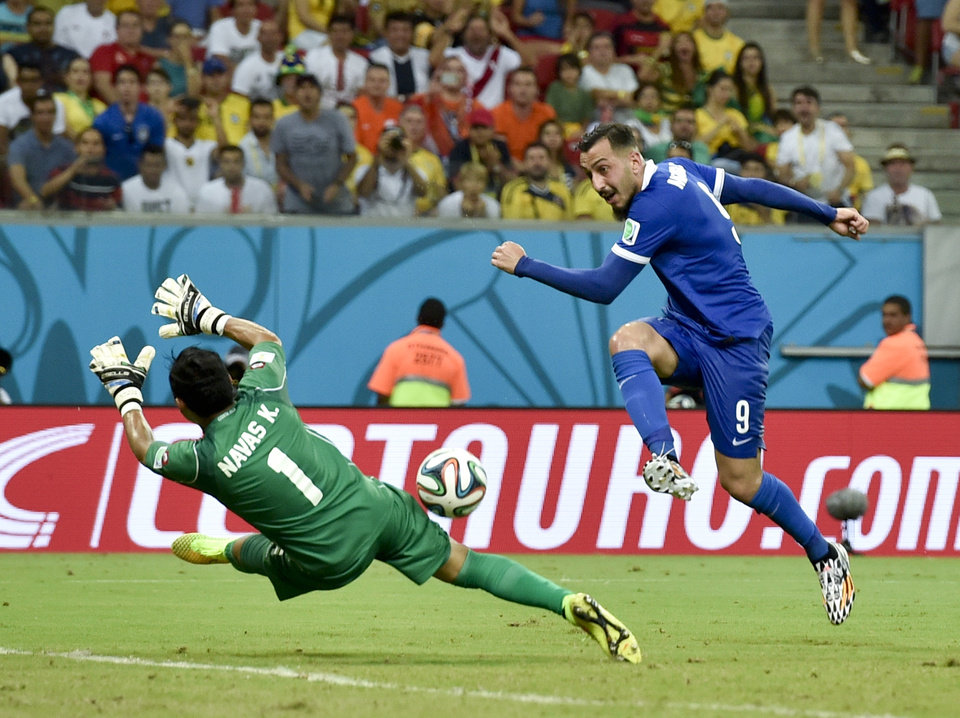 Photo - Costa Rica's goalkeeper Keylor Navas makes a save on a shot by Greece's Kostas Mitroglou during extra time in the World Cup round of 16 soccer match between Costa Rica and Greece at the Arena Pernambuco in Recife, Brazil, Sunday, June 29, 2014. (AP Photo/Martin Meissner)