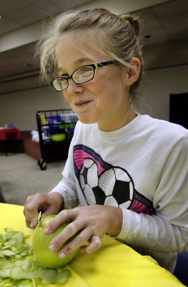 Abbey Colijn, 12, peels apples as kids make apple pies for Thanksgiving in an Apple Pie 101 workshop at the Norman Public Library on Wednesday, Nov. 21, 2012, in Norman, Okla. Photo by Steve Sisney, The Oklahoman