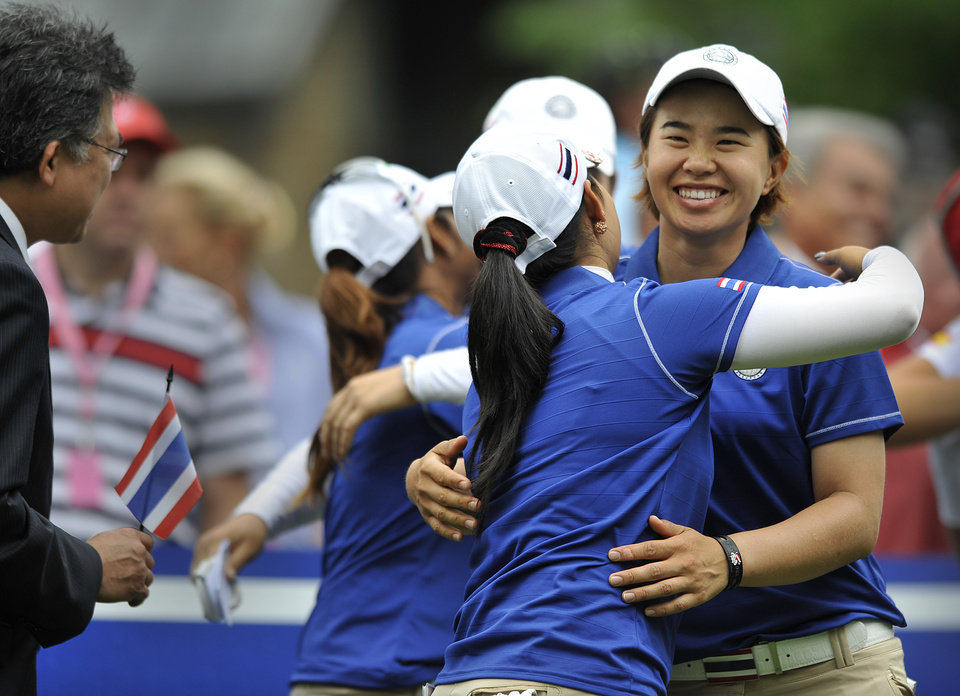 Photo - Onnarin Sattayabanphot, right, is hugged by Pornanong Phatlum, both of Thailand, hug before the first round of the International Crown LPGA golf tournament Thursday, July 24, 2014, in Owings Mills, Md.(AP Photo/Gail Burton)