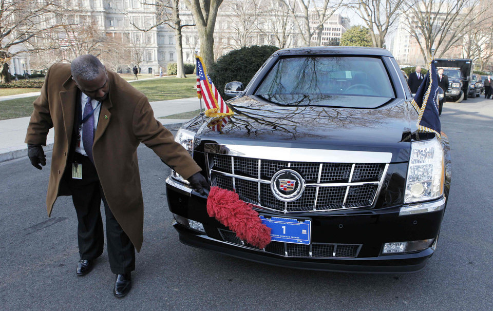 Photo - A Secret Service agent readies the new presidential limousine that will take President George W. Bush and President-elect Barack Obama from the White House to the inauguration ceremony at the Capitol in Washington, Tuesday, Jan. 20, 2009. (AP Photo/Charles Dharapak)