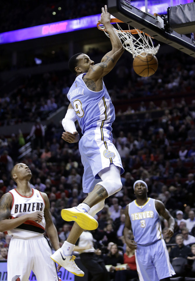 Denver Nuggets guard Andre Iguodala, center, scores on a fast break as Portland Trail Blazers guard Damian Lillard, left, and Nuggets guard Ty Lawson watch during the first quarter of an NBA basketball game in Portland, Ore., Wednesday, Feb. 27, 2013. (AP Photo/Don Ryan)