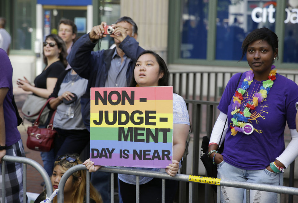 Photo - Eliza Galimba, 16, holds up a sign while watching the 44th annual San Francisco Gay Pride parade Sunday, June 29, 2014, in San Francisco. The lesbian, gay, bisexual, and transgender celebration and parade is one of the largest LGBT gatherings in the nation. (AP Photo/Eric Risberg)