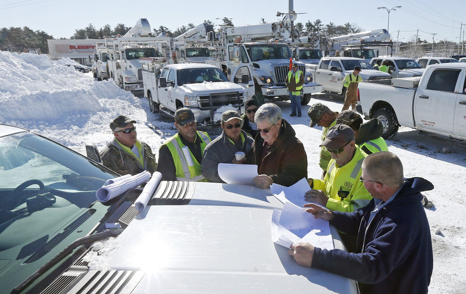 With more than a hundred trucks waiting to deploy, National Grid and utility workers from South Carolina meet on the hood of a pick-up truck to discuss their plan to re-energize towns without power at the Hanover Mall in Hanover, Mass., Sunday, Feb. 10, 2013.  A howling storm across the Northeast left the New York-to-Boston corridor shrouded in 1 to 3 feet of snow Saturday, stranding motorists on highways overnight and piling up drifts so high that some homeowners couldn't get their doors open. More than 650,000 homes and businesses were left without electricity. (AP Photo/Charles Krupa)