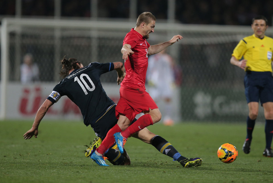 Photo - Turkey's Caner Erkin, left, clashes with Sweden's Zlatan Ibrahimovic during their International Friendly soccer match at 19 Mayis Stadium in Ankara, Turkey, Wednesday, March 5, 2014.(AP Photo)