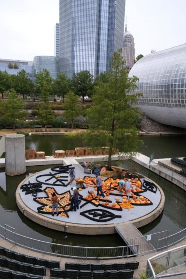 Photo -  Local artist Nick Bayer gets help building a giant pumpkin mural on the Water Stage for the Myriad Botanical Gardens' Great Pumpkin Patch. [Doug Hoke/The Oklahoman]