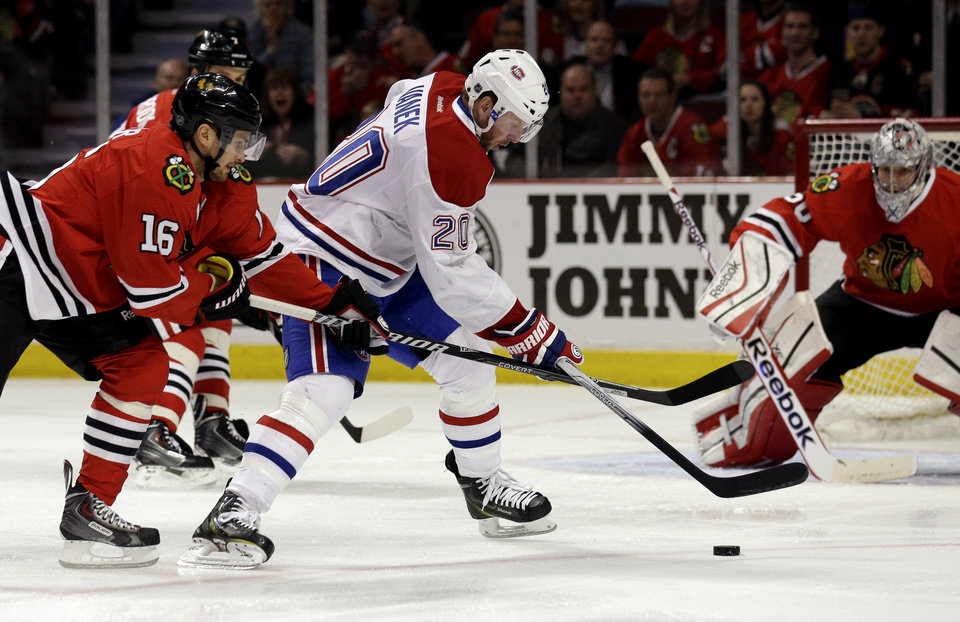 Photo - Montreal Canadiens' Thomas Vanek (20) controls the puck against Chicago Blackhawks' Marcus Kruger (16) during the first period of an NHL hockey game in Chicago, Wednesday, April 9, 2014. (AP Photo/Nam Y. Huh)