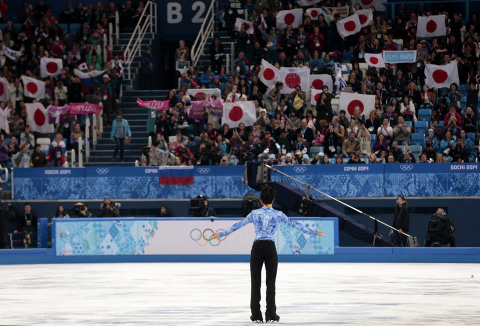 Photo - Yuzuru Hanyu of Japan acknowledges the crowd after the men's short program figure skating competition at the Iceberg Skating Palace during the 2014 Winter Olympics, Thursday, Feb. 13, 2014, in Sochi, Russia. (AP Photo/Ivan Sekretarev)