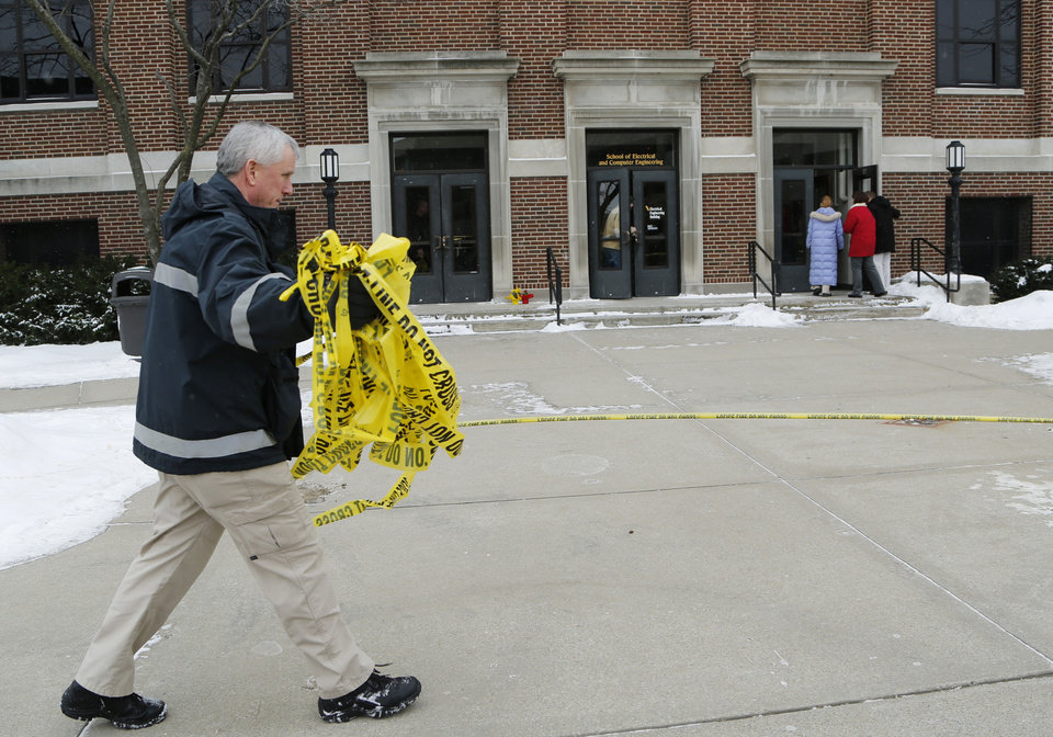 Photo - Kevin Luse of Purdue University Fire Department collects police tape as the Electrical Engineering building is opened, Wednesday, January 22, 2014, on the campus of Purdue University, in West Lafayette, Ind. The building had been closed since engineering student Andrew Boldt was shot and killed Tuesday. Cody Cousins, a student, has been charged in the shooting.  (AP Photo/Journal & Courier, John Terhune)