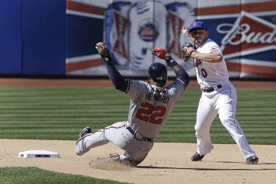 Photo - New York Mets shortstop Omar Quintanilla, right, turns a double play over Atlanta Braves' Jason Heyward during the seventh inning of the baseball game, Sunday, April 20, 2014 in New York. (AP Photo/Seth Wenig)
