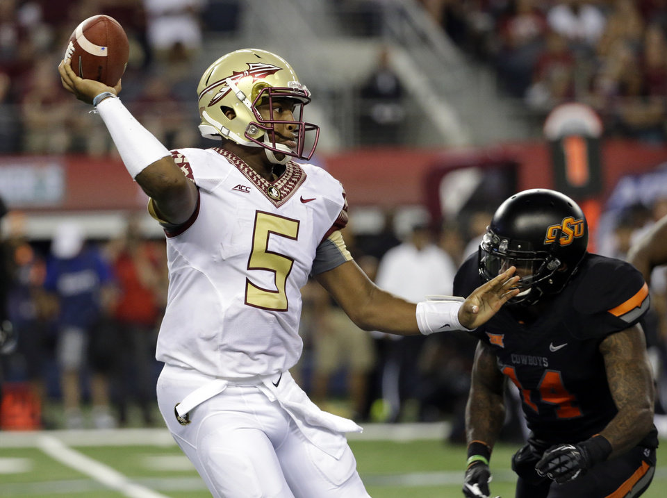 Photo - Florida State quarterback Jameis Winston (5) passes under pressure from Oklahoma State linebacker Josh Furman (14) during an NCAA college football game, Saturday, Aug. 30, 2014, in Arlington, Texas. (AP Photo/Tony Gutierrez)