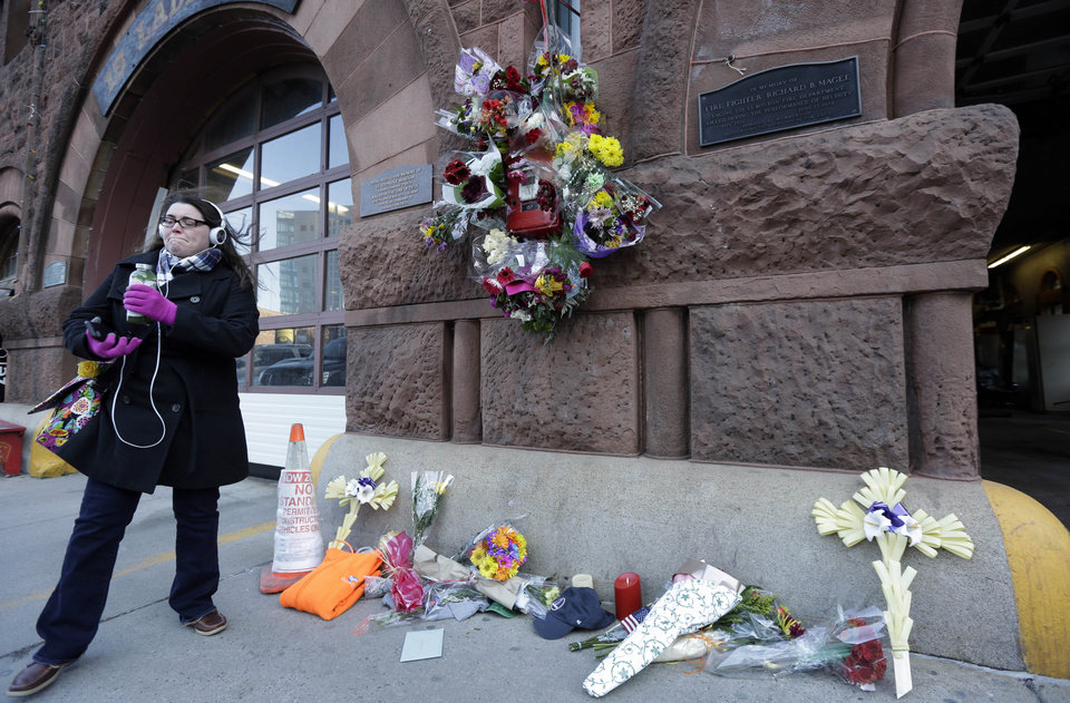 Photo - Erin Defuria, of Boston, is emotional after placing flowers at a makeshift memorial in the front of fire station Engine 33/Ladder 15, Thursday, March 27, 2014, in Boston. Engine 33/Ladder 15 was the station of fallen firefighters Lt. Edward Walsh and Michael Kennedy who lost their lives fighting a nine-alarm blaze in a four-story brownstone in Boston's Back Bay neighborhood Wednesday, March 26, 2014. (AP Photo/Steven Senne)