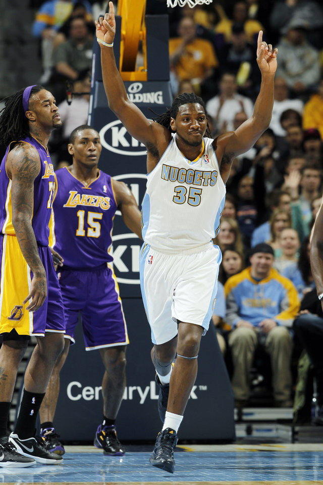 Photo - Denver Nuggets forward Kenneth Faried (35) celebrates after tipping the ball in to score as Los Angeles Lakers center Jordan Hill, left, and forward Metta World Peace (15) stand by in the first quarter of an NBA basketball game in Denver, Wednesday, Dec. 26, 2012. (AP Photo/David Zalubowski)