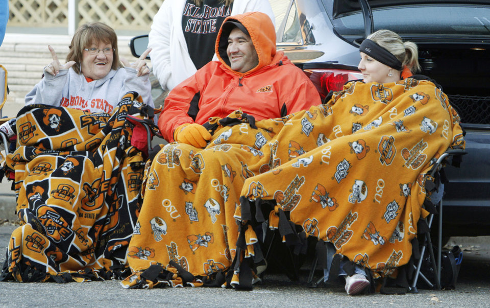 Photo - Melissa (left), Terry, and Jessica Kennedy bundle up to watch the Oklahoma State Cowboy's homecoming parade in downtown Stillwater, OK, Saturday, Oct. 29, 2011. By Paul Hellstern, The Oklahoman