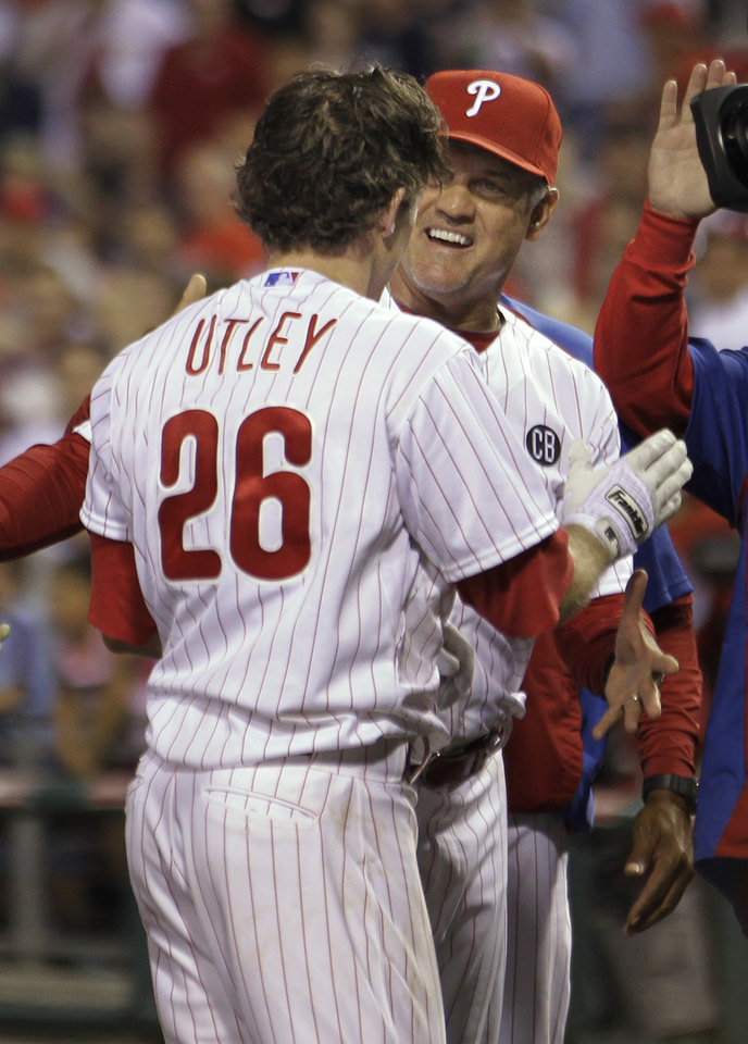 Photo - Philadelphia Phillies' Chase Utley is greeted by manager Ryne Sandberg after hitting the game-winning two-home run in the 14th inning of a baseball game against the Miami Marlins, Thursday, June 26, 2014, in Philadelphia. The Phillies won 5-3. (AP Photo/Laurence Kesterson)