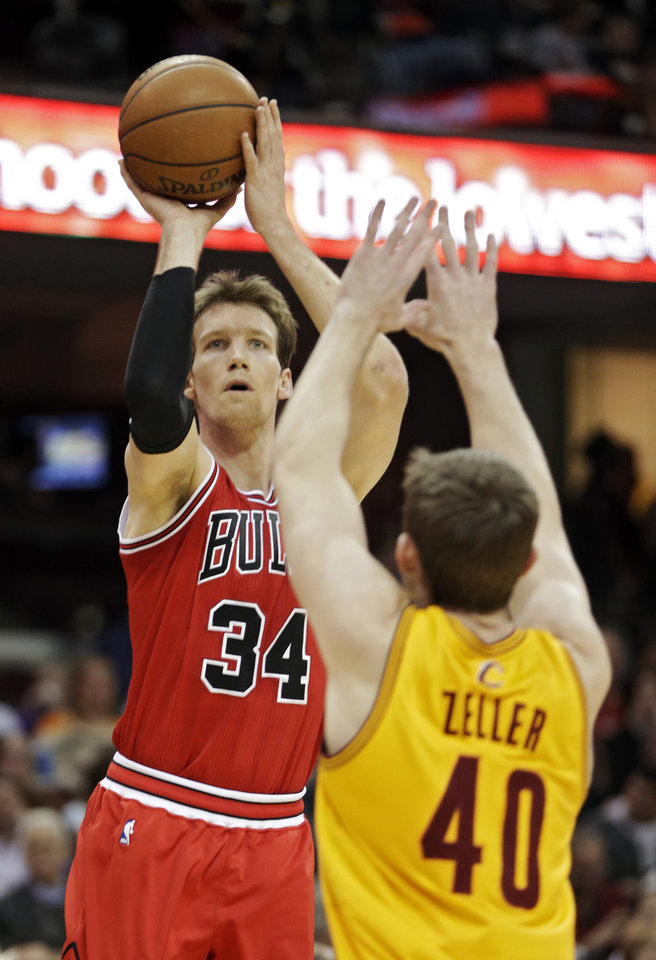 Photo - Chicago Bulls' Mike Dunleavy (34) shoots a three-point shot over Cleveland Cavaliers' Tyler Zeller (40) in the second quarter of an NBA basketball game Wednesday, Jan. 22, 2014, in Cleveland. (AP Photo/Mark Duncan)