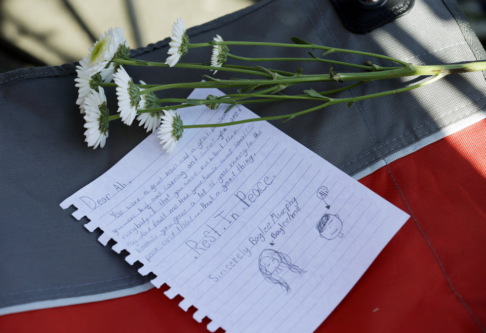 Photo - A letter of tribute and flowers sit on a chair as fans await the funeral procession for Muhammad Ali to make its way down Muhammad Ali Boulevard in Louisville, Ky. Friday, June 10, 2016. (AP Photo/Michael Conroy)
