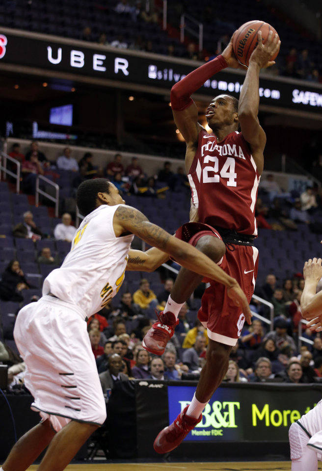 Photo - Oklahoma guard Buddy Hield (24) shoots over George Mason guard Sherrod Wright (10) during the first half of an NCAA college basketball game in the BB&T Classic, Sunday, Dec. 8, 2013, in Washington. (AP Photo/Alex Brandon)