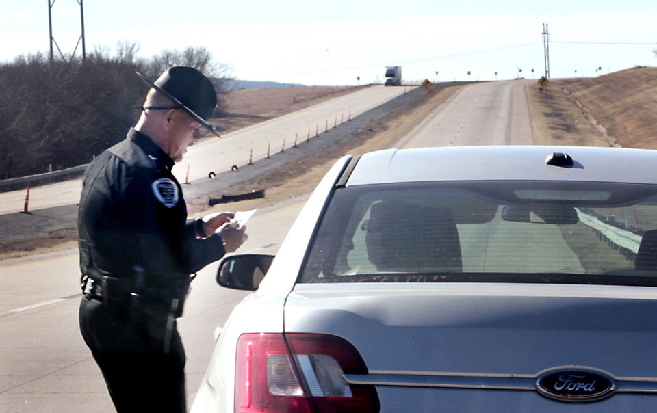 Photo - Kiowa Police Department Chief Tony Runyon makes a traffic stop Friday on U.S. 69 in Kiowa and writes a ticket. Photo by David McDaniel, The Oklahoman  David McDaniel