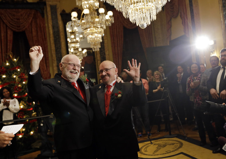 Photo - James Scales, left, and William Tasker react after participating in a wedding ceremony at City Hall in Baltimore, Tuesday, Jan. 1, 2013. Same-sex couples in Maryland are now legally permitted to marry under a new law that went into effect after midnight on Tuesday. Maryland is the first state south of the Mason-Dixon Line to approve same-sex marriage. (AP Photo/Patrick Semansky)
