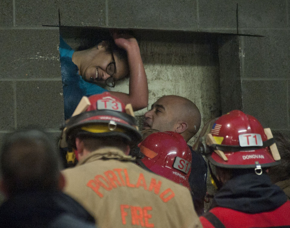 Photo - A woman is rescued from being trapped inside a wall of the parking garage at the Gretchen Kafoury Commons in SW Portland, Ore., Wednesday, Jan. 16, 2013. Portland firefighters worked for over three and a half hours cutting her free. (AP Photo/The Oregonian, Brent Wojahn)