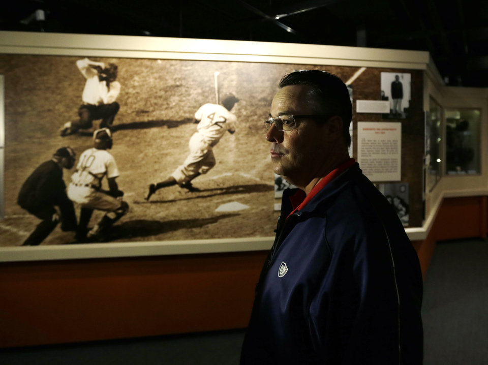 Photo - Former Atlanta Braves pitcher Greg Maddux visits a Jackie Robinson exhibit during his orientation visit at the Baseball Hall of Fame on Monday, March 24, 2014, in Cooperstown, N.Y. Maddux will be inducted to the hall in July. (AP Photo/Mike Groll)
