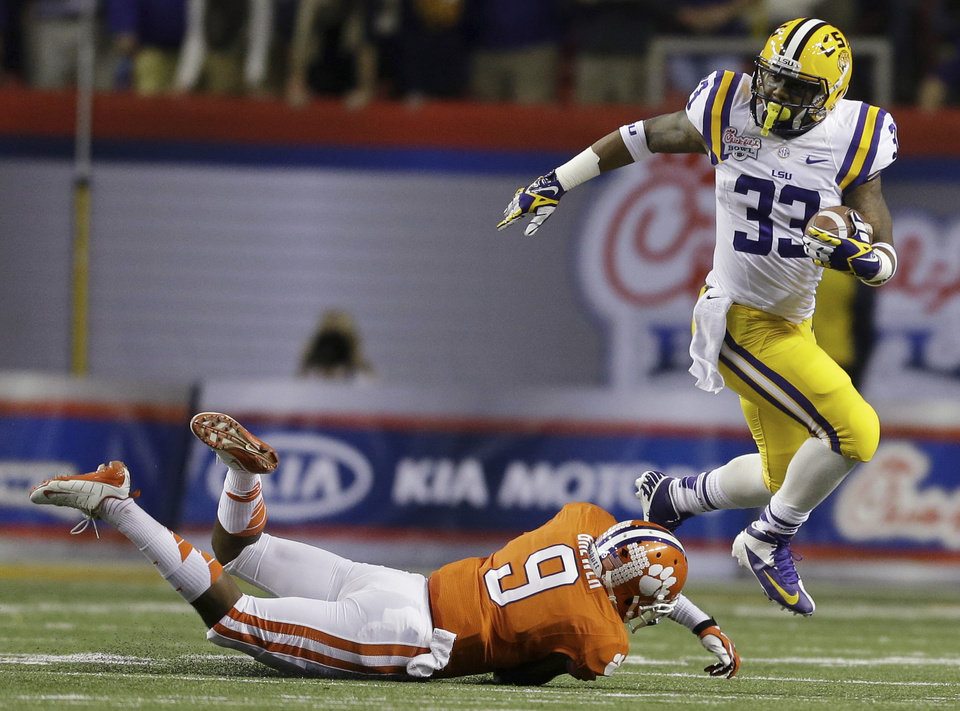 Photo - LSU running back Jeremy Hill (33) runs past Clemson defensive back Xavier Brewer (9) during the first half of the Chick-fil-A Bowl NCAA college football game, Monday, Dec. 31, 2012, in Atlanta. (AP Photo/David Goldman)