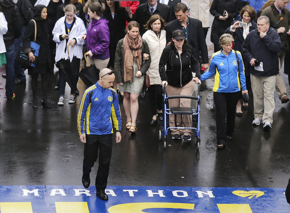 Photo - Marathon survivor Erika Brannock, a teacher from Maryland, uses a walker as she prepares to cross the finish line following a tribute in honor of the one year anniversary of the Boston Marathon bombings, Tuesday, April 15, 2014 in Boston. (AP Photo/Charles Krupa)