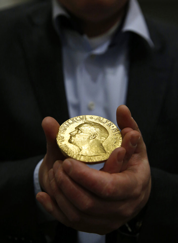 Photo - Bidder Ole Bjorn Fausa, of Norway, holds the 1936 Nobel Peace Prize medal in Baltimore, Thursday, March 27, 2014, the second Nobel Peace Prize ever to come to auction. It was won by an anonymous telephone bidder for $950,000. The recipient was Argentina's foreign minister, Carlos Saavedra Lamas, who was honored for his role in negotiating the end of the Chaco War between Paraguay and Bolivia. (AP Photo/Patrick Semansky)