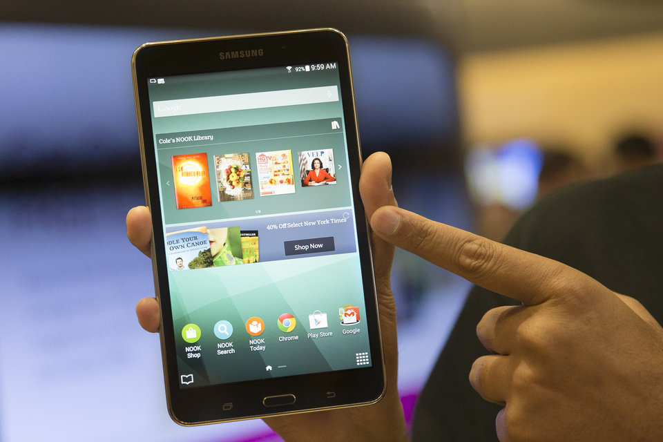 Photo - A brand ambassador handles a new Samsung Galaxy Tab 4 Nook during the unveiling of the co-branded tablet that will replace B&N's Nook, Wednesday, Aug. 20, 2014, in New York. The 7-inch tablet will sell for $179 after a $20 instant rebate, the same entry price of the non-branded Samsung Galaxy Tab 4. (AP Photo/John Minchillo)