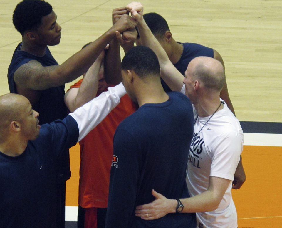 ADVANCE FOR WEEKEND EDITIONS, APRIL 7-8 - In this photo taken April 5, 2012, new Illinois basketball coach John Groce, right, huddles with some members of his new team and new assistant coach Jamall Walker, left, before practice in Champaign, Ill. Groce was hired last month from Ohio University to replace Bruce Weber. (AP Photo/David Mercer)