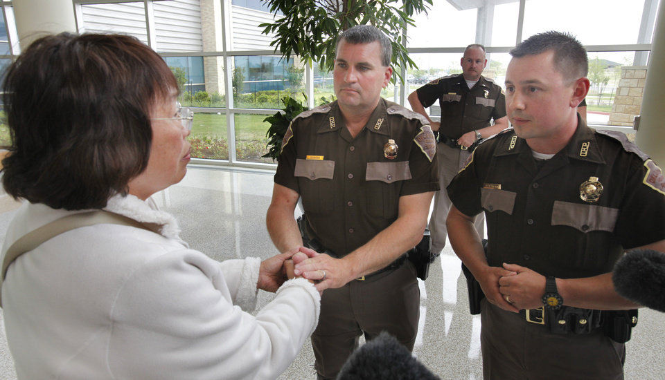 Photo - Nenita Mijares thanks Oklahoma Highway Patrol troopers Steve Johnson and Ken Pittman in April 2011 after the troopers performed CPR on her husband, Hector Mijares, while working a multivehicle accident along Interstate 35 in Moore.  Photo by Steve Sisney, The Oklahoman Archives