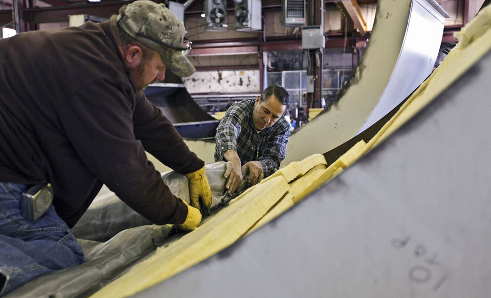 Photo - David Fessler, right, and Blaine Jernigan install acoustic pillows in a section of a jet engine test cell at Swanda Brothers in Oklahoma City.  CHRIS LANDSBERGER - CHRIS LANDSBERGER