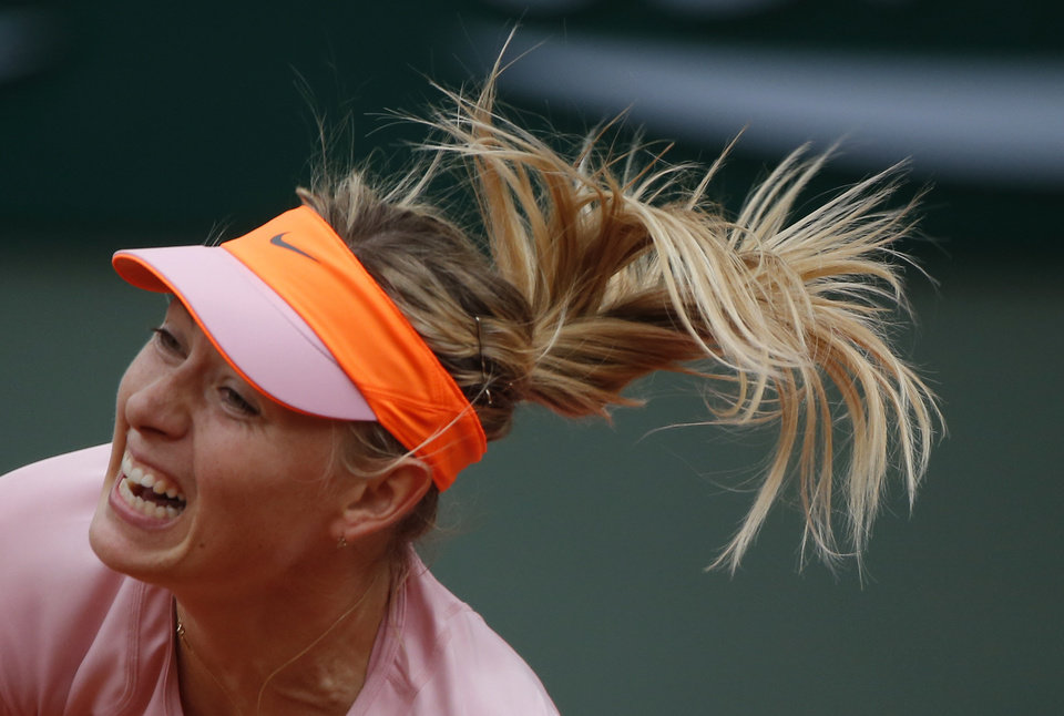 Photo - Russia's Maria Sharapova serves the ball to compatriot Ksenia Pervak during their first round match of  the French Open tennis tournament at the Roland Garros stadium, in Paris, France, Monday, May 26, 2014. Sharapova won 6-1, 6-2.  (AP Photo/Michel Euler)
