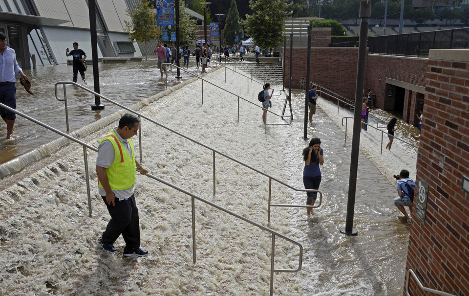 Photo - People walk down a stairway leading to a parking structure across from Pauley Pavilion on the UCLA campus after flooding from a broken 30-inch water main under nearby Sunset Boulevard inundated a large area of the campus in the Westwood section of Los Angeles, Tuesday, July 29, 2014. The 30-inch (75-centimeter)  93-year-old pipe that broke made a raging river of the street and sent millions of gallons (liters) of water across the school's athletic facilities, including the famed floor of Pauley Pavilion, the neighboring Wooden Center and the Los Angeles Tennis Center, and a pair of parking structures that took the brunt of the damage. (AP Photo/Mike Meadows)