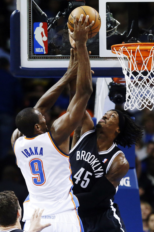 Photo - Oklahoma City Thunder forward Serge Ibaka (9) shoots as Brooklyn Nets forward Gerald Wallace (45) defends in the second quarter of an NBA basketball game in Oklahoma City, Wednesday, Jan. 2, 2013. (AP Photo/Sue Ogrocki)