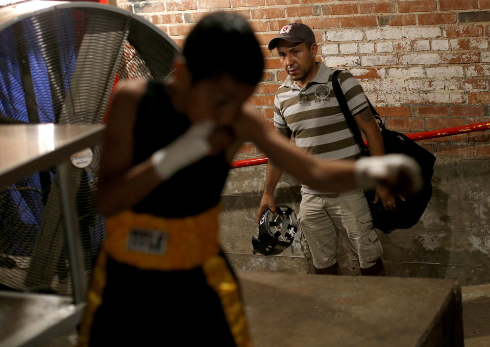 Felipe Barba watches his son, Chris Barba, 9, of Edmond, warm up before his first fight at The Underground Arena in Oklahoma City, Saturday, June 15, 2013. Chris, who started training with Azteca Boxing Club 1 1/2 months ago, won his first fight. Chris' journey to his first fight started when offered gas money to a family friend if he would take him to the boxing gym. After visiting the gym a few times he told his father Felipe he wanted to box. Chris' father drives from his job in Norman, back to Edmond to take his son to Azteca Boxing Gym on SW 25th Street five days a week. He said it's worth the long round trip because his son enjoys it and is excited to put the time and effort into training. Photo by Bryan Terry, The Oklahoman