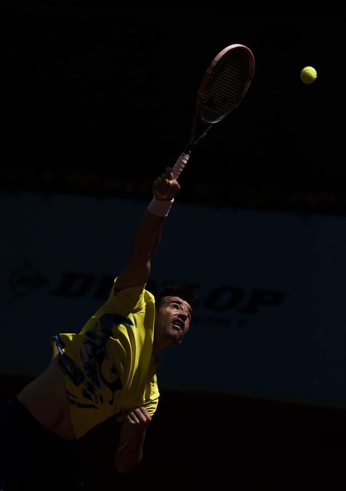 Photo - Ivan Dodig from Croatia serves during a Madrid Open tennis tournament match against Kei Nishikori from Japan, in Madrid, Spain, Monday, May 5, 2014. (AP Photo/Andres Kudacki)