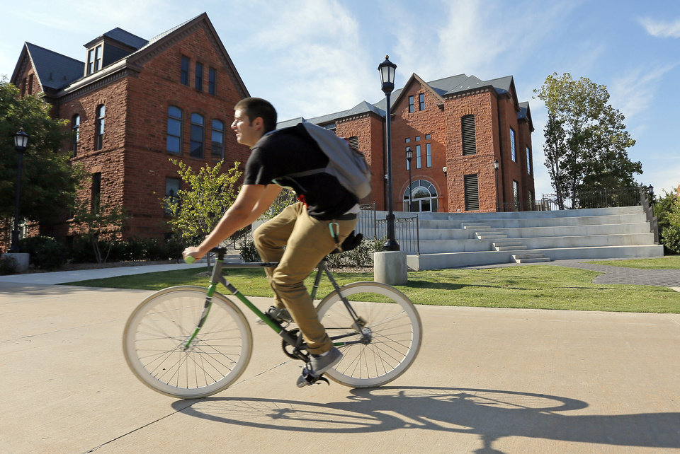 A cyclist rides past the east side of Old North on the campus of the University of Central Oklahoma, in Edmond, Okla., Monday, Aug. 20, 2012. Photo by Nate Billings, The Oklahoman