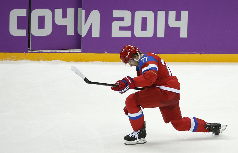 Photo - Russia defenseman Anton Belov reacts after scoring a goal against Slovenia in the third period of a men's ice hockey game at the 2014 Winter Olympics, Thursday, Feb. 13, 2014, in Sochi, Russia. (AP Photo/Mark Humphrey)