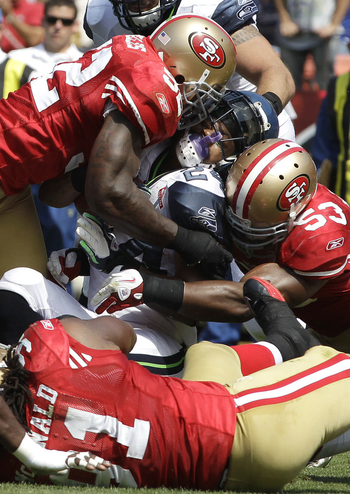 FILE - In this Sept. 11, 2011 file photo, San Francisco 49ers linebackers Patrick Willis (52),backer NaVorro Bowman (53), and defensive tackle Ray McDonald (91) tackling Seattle Seahawks running back Marshawn Lynch (24) during the first quarter of an NFL football game in San Francisco. They are not only the biggest reason behind the 49ers' defensive success, they are a close bunch that has quickly become the new NFL standard for linebackers. Meet Patrick Willis, NaVorro Bowman, Aldon Smith and Ahmad Brooks. (AP Photo/Paul Sakuma, File)